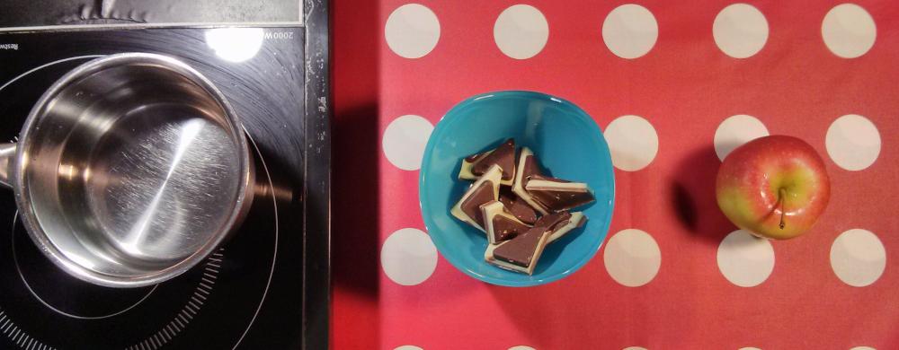Ein Töpfchen mit Wasser, ein Schälchen mit Schokoladestückchen, ein Apfel.